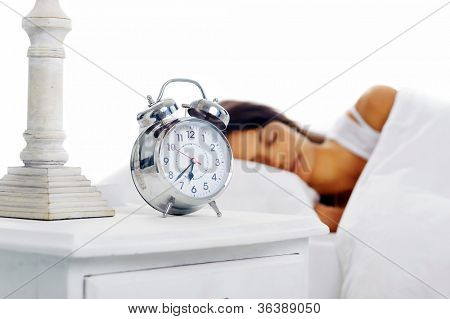 Beautiful sleeping woman resting in bed with alarm clock ready to wake her in the morning.