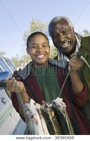 Portrait of young boy with grandfather holding freshly caught fishes