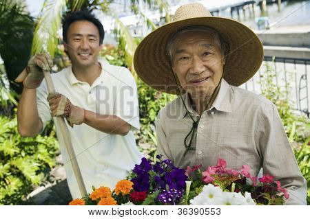 Portrait of a happy elderly man with son working in garden