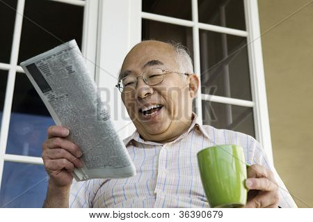Cheerful senior man with coffee cup reading newspaper in front of house