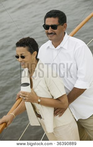 Happy couple on yacht with woman having coffee