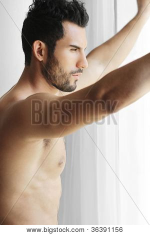 Portrait of a thoughtful handsome naked young man looking out of a window thinking
