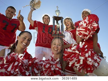 Portrait of excited players with cheerleaders holding trophy against clear sky