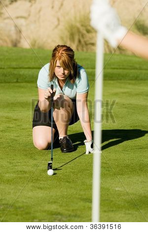 Woman crouches and lines up her putt on a golf course