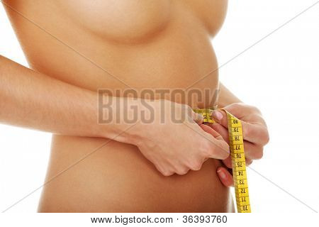 Naked woman measuring her weist.