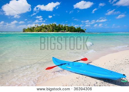 Colorful kayak in a tropical lagoon with small island on background