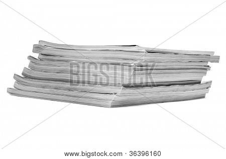 closeup of a pile of different magazines on a white background