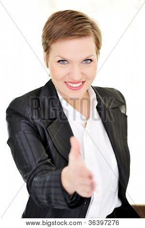 Young happy business woman at office gives a handshake