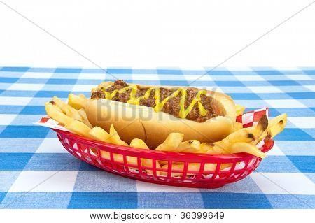 Side view of a chilidog with french fries on a checkered tablecloth.  Image was set up so designers can drop in any background they wish.