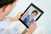 stock photo of video chat  - A young couple talking to each other via online video Skype on Apple Ipad - JPG