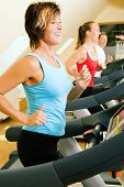 stock photo of gym workout  - Three happy people running on a treadmill in a gym - JPG