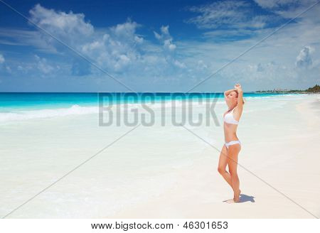 Beautiful slim woman tanning on the beach, standing on clean white sand, taking sunbath, enjoying dayspa, summer holiday and vacation concept