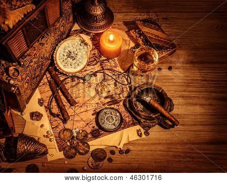 Closeup of pirates booty on wooden table, cigars smoke, glass of wine, map with way to search treasure, stolen antique jewelry, ancient money, adventure concept