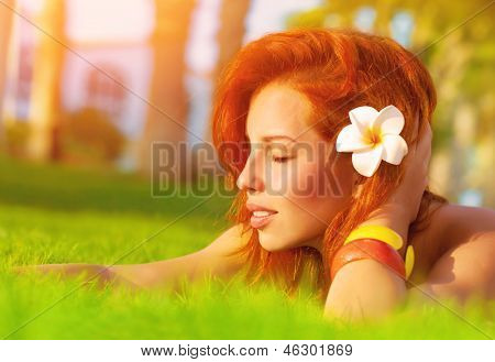 Profile of attractive woman with closed eyes dreaming outdoors, lying down on fresh green grass glade, frangipani flower in red hair, enjoying day spa, luxury summer resort