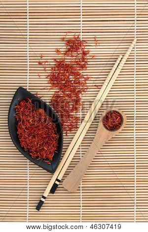 Saffron spice used in chinese herbal medicine and cooking over bamboo background.