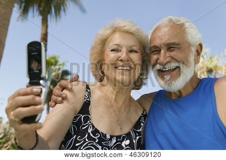 Senior woman using mobile phone photographing self with husband outdoors.