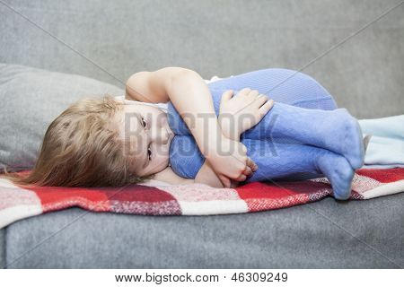 Caucasian wehrlos Kleinkind zusammengedrängt auf der Couch