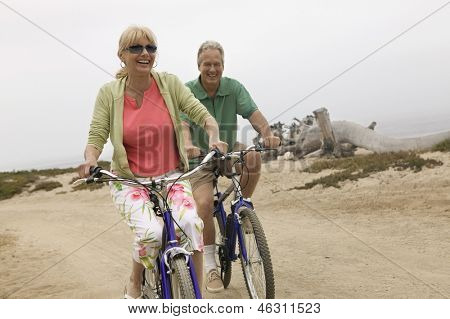 Cheerful middle aged couple riding bicycles along the beach