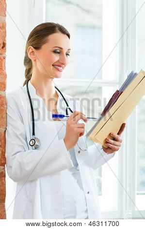 Young female doctor standing at a window in clinic writing in a file or dossier