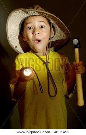 Boy Exploring With Flashlight And Hammer