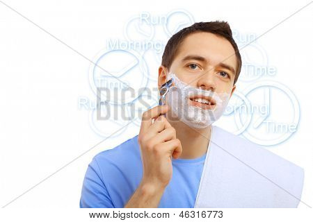 Young man in blue T-shirt shaving himself