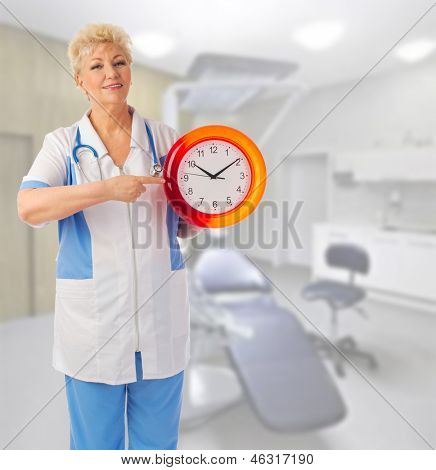 Mature doctor with clock at medical office