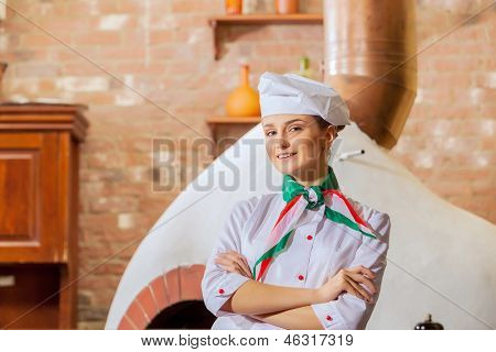 Image of young woman cook standing at kitchen