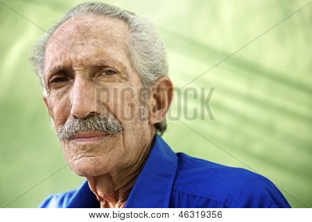 Portrait Of Serious Old Hispanic Man Looking At Camera