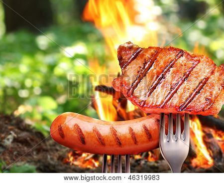 Sausage and steak on a fork. In the background a bonfire in the forest.