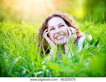 Beautiful Young Woman Outdoors Enjoying Nature. Healthy Smiling Girl Relaxing in Green Grass