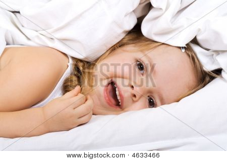 Little Girl Laying In Bed Under The Quilt