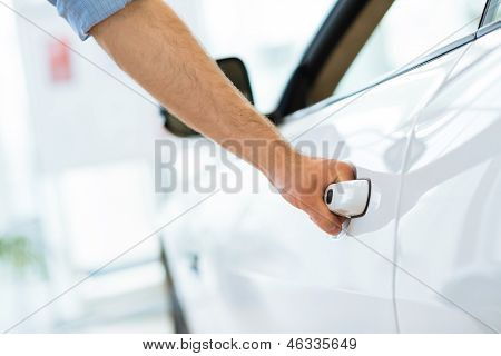 man opens the door to a new car