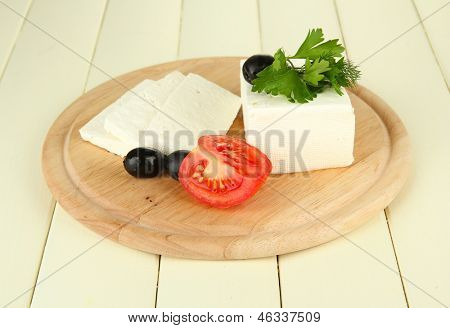 Sheep milk cheese, black olives, red tomato with parsley and dill on cutting board, on color wooden background