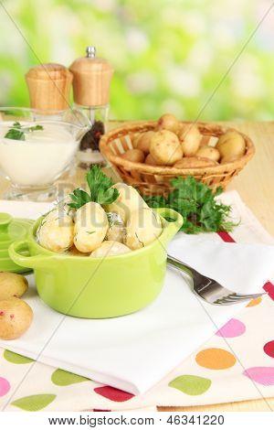 Concursos jovens batatas com creme de leite e ervas na panela sobre a mesa de madeira no fundo natural