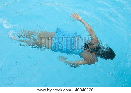 Girl Is Swimming Under Water In Waterpool
