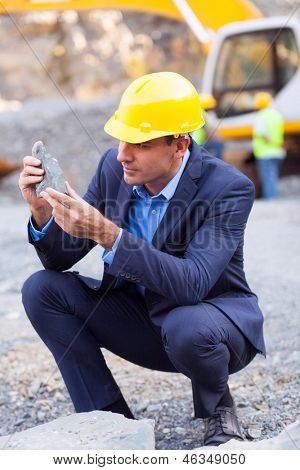 mine manager inspecting ore on site