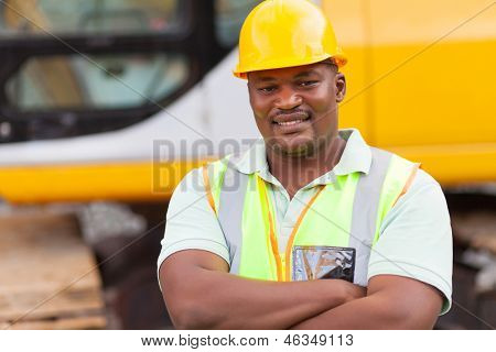 smiling african mine worker with arms folded at mining site