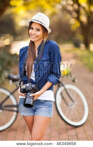 beautiful young girl posing with her photo camera at the park