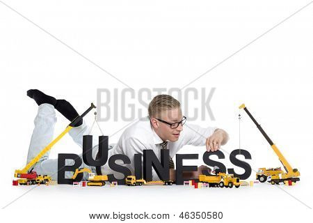 Business start up concept: Joyful businessman building the word business along with construction machines, isolated on white background.