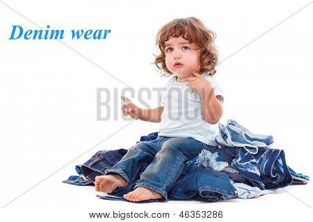 Lovely curly child sitting on the jeans pile