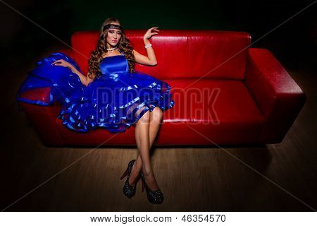 Alluring woman in blue dress sitting on red leather divan