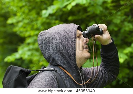 Man with binoculars watching birds in the park