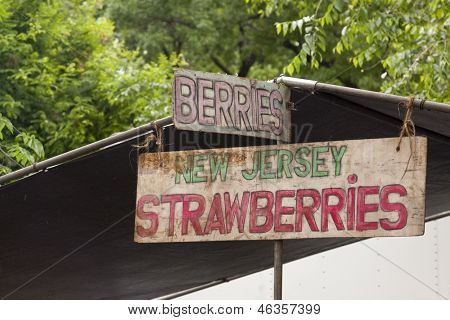 A wooden sign at a farmers market that reads New Jersey Strawberries.