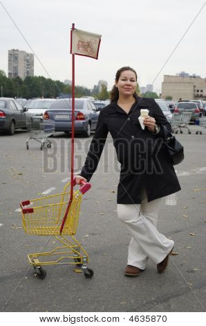 Pregnant Woman With Shopping Trolley And Ice Cream
