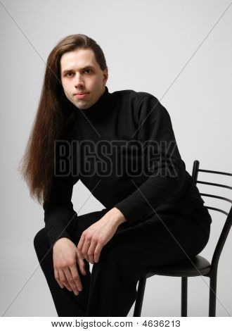 Young Man With Long Hair In Black