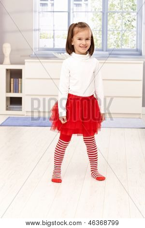 Happy little girl standing in middle of living room, smiling.