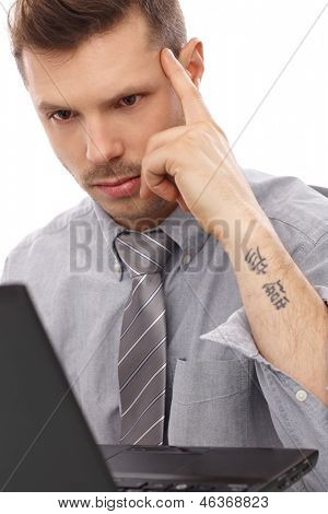 Trendy businessman with tattoo working on laptop computer.
