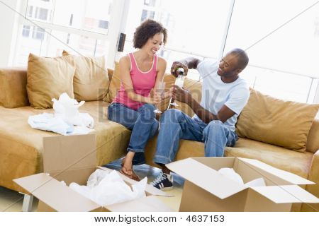 Couple relaxing mit Champagner von Boxes in new home smiling
