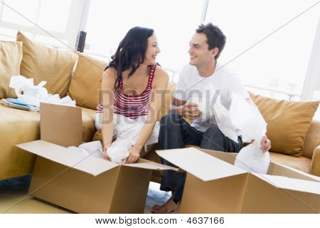 Couple Unpacking Boxes In New Home Smiling