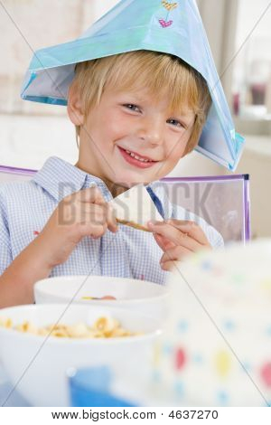 Young Boy At Party Sitting At Table With A Sandwich Smiling